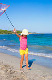 Little happy girl playing with flying kite during Stock Images