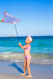 Little happy girl playing with flying kite during Stock Photo