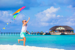 Little happy girl playing with flying kite on Stock Photos