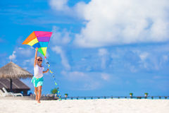 Little happy girl playing with flying kite on Stock Photography