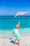 Little happy girl playing with flying kite on tropical beach Royalty Free Stock Photos
