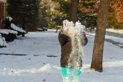 Little happy girl playing at snowy winter outdoor. Little girl playing with snow outdoors Royalty Free Stock Image