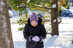 Little happy girl playing at snowy winter outdoor Royalty Free Stock Images