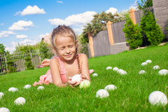 Little happy girl playing with white Easter eggs Royalty Free Stock Image