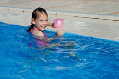Happy girl in the pool with ball Royalty Free Stock Photography