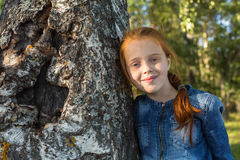 Little happy girl portrait near tree birch. Stock Image