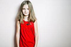 Little happy girl posing in a red dress. Stock Photo