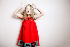 Little happy girl posing in a red dress. Royalty Free Stock Photos
