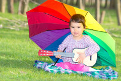 Little happy girl with a rainbow umbrella and guitar in thepark Stock Images