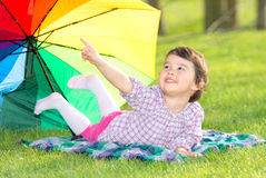 Little happy girl with a rainbow umbrella in the park Royalty Free Stock Images
