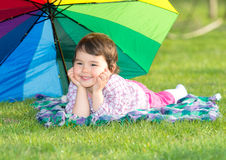 Little happy girl with a rainbow umbrella in the park Stock Photography