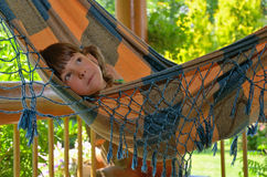 Little happy girl relaxing in hammock Stock Photo