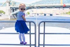 Little happy girl relaxing on luxury ship sailing in the big city Stock Photography