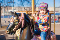 Little happy girl riding on carousel at an amusement park Stock Images