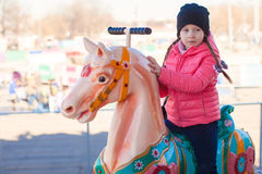 Little happy girl riding on carousel at an amusement park Royalty Free Stock Photo