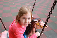 Little happy girl riding on carousel at an amusement park Royalty Free Stock Image