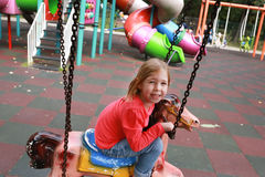 Little happy girl riding on carousel at an amusement park Stock Photography