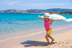 Little happy girl running on beach with towel Royalty Free Stock Images