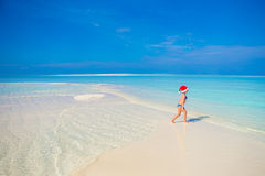 Little happy girl in Santa hat during beach Royalty Free Stock Images