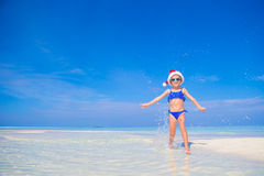Little happy girl in Santa hat during beach Stock Photo