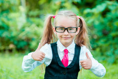 Little happy girl showing thumbs up. Back to school outdoor Stock Photos