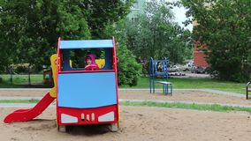 Little happy girl sits in colored wooden car at playground stock footage