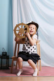 Little happy girl sits with steering wheel and plays sailor Stock Image