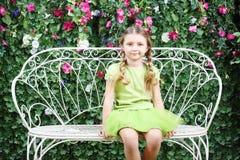 Little happy girl sits on white retro bench. Near verdant hedge Royalty Free Stock Image