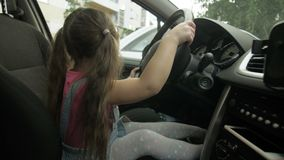 A little happy girl is sitting behind the wheel of a car. Portrait of a child in a new car driving stock footage