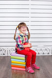 Little happy girl sitting on pile of books. Royalty Free Stock Photo