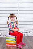 Little happy girl sitting on pile of books. Stock Photo