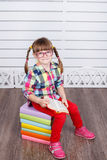 Little happy girl sitting on pile of books. Stock Photos