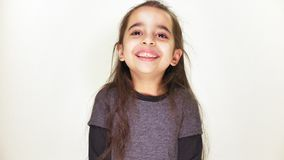 Little happy girl smiling, laughing and looking at the camera, portrait, white background 50 fps stock video footage