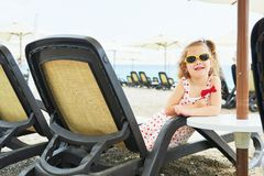 Little happy girl on the sunbeds by the sea, posing for the camera Royalty Free Stock Images