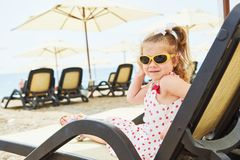 Little happy girl on the sunbeds by the sea, posing for the camera Stock Photos