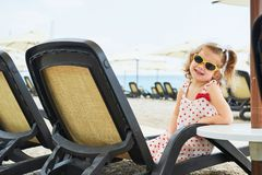 Little happy girl on the sunbeds by the sea, posing for the camera Royalty Free Stock Photo