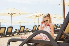 Little happy girl on the sunbeds by the sea, posing for the camera Royalty Free Stock Photography