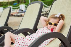 Little happy girl on the sunbeds by the sea, posing for the camera Stock Images