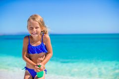 Little happy girl with suntan lotion bottle during Stock Image