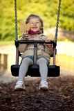 Little happy girl on the swing Royalty Free Stock Images