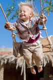 Little happy girl on a swing with closed eyes Stock Photos