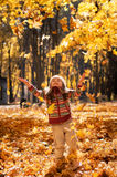 Little happy girl throws up fallen leaves Royalty Free Stock Image