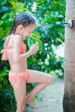 Little happy girl under beach shower on tropical beach. Little cute girl under beach shower on tropical beach Stock Images