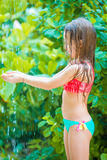 Little happy girl under beach shower on tropical beach. Little cute girl under beach shower on tropical beach Stock Photo