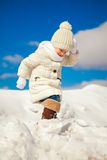 Little happy girl is walking in the snow on a Royalty Free Stock Images