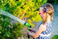 Little happy girl watering garden royalty free stock photo