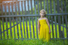 Little happy girl in yellow dress near the wooden fence in the village. Royalty Free Stock Image