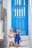 Little happy girls in dresses at street of typical greek traditional village on Mykonos Island, in Greece. Little happy girls in dresses at street of typical stock photos