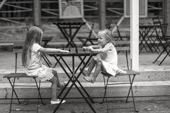 Little happy girls have fun at outdoor cafe Stock Image