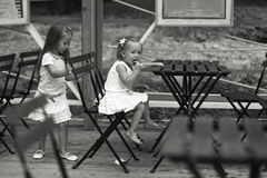 Little happy girls have fun at outdoor cafe Stock Photo
